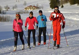 A group of skiers is following their ski instructor from the ski school ESF Chamonix during their Cross-Country Skiing Lessons for Adults - All Levels.