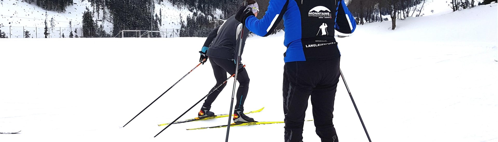An instructor is watching the participants' progress and giving tips during the Trial Cross Country Skiing Lessons - Beginners with Skischule Monntains.