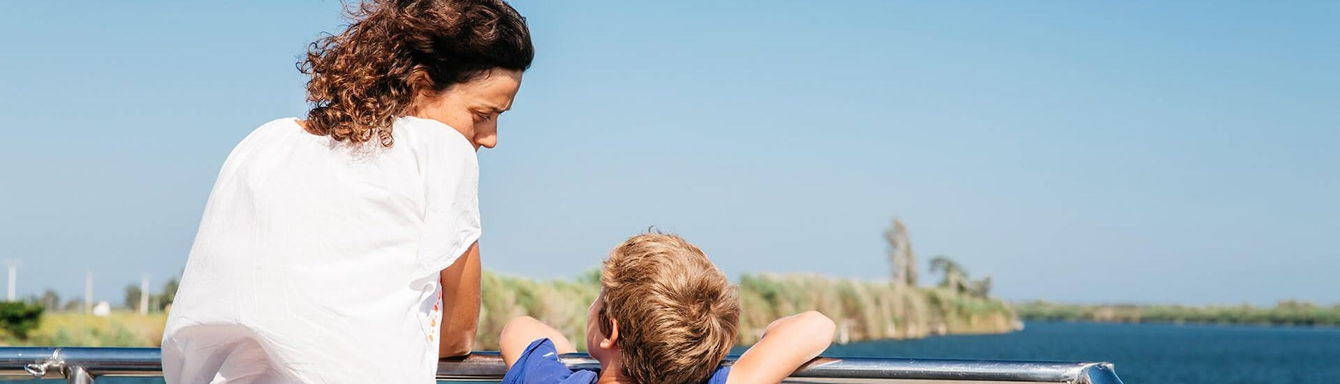 A mother and her son enjoy the great view during a Boat Tour at the Ebro Delta River organized by Estació Nàutica Costa Daurada.