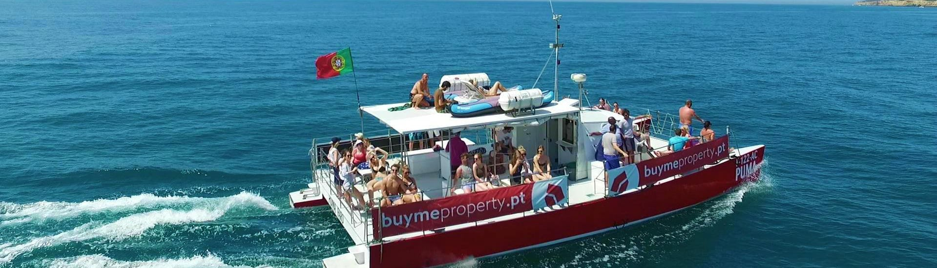 The passengers of a boat tour with Cruzeiros da Oura Vilamoura are enjoying the sun on board of the boat as they cruise along the Algarve Coast.