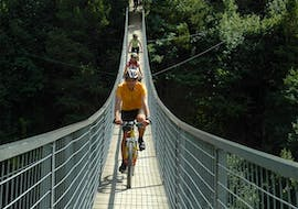 Three cyclists are crossing a bridge during their Mountain Bike Tour on the Ötztal Trail with CanKick Ötztal.