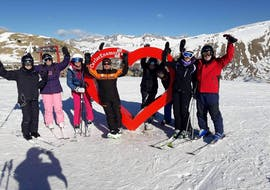 A group of adult skiers stand in the middle of the ski area and look forward to their Ski Lesson for Adults - All Levels with the ski school Escuela Esquí y Snowboard Valle de Benás.