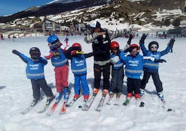A group of kids happily throws their arms up in the air during their kids ski lessons (4-16 years) - All Levels of ski school Escuela Esquí y Snowboard Valle de Benás.