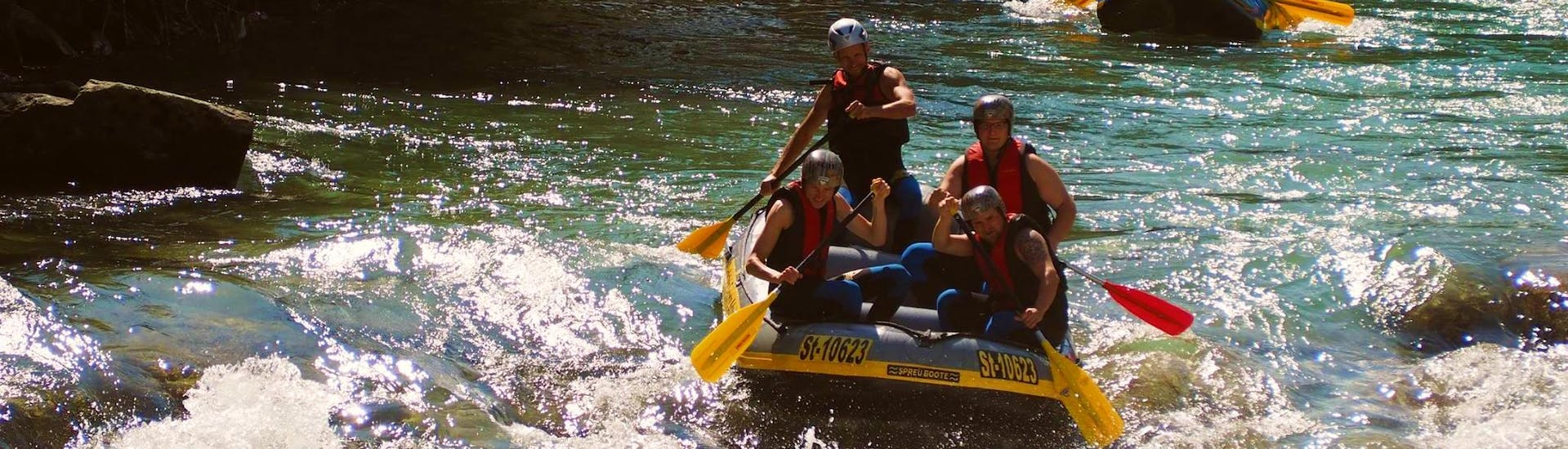 A group of friends is enjoying their rafting tour on the Enns river with Dachstein Tauern Adventure.