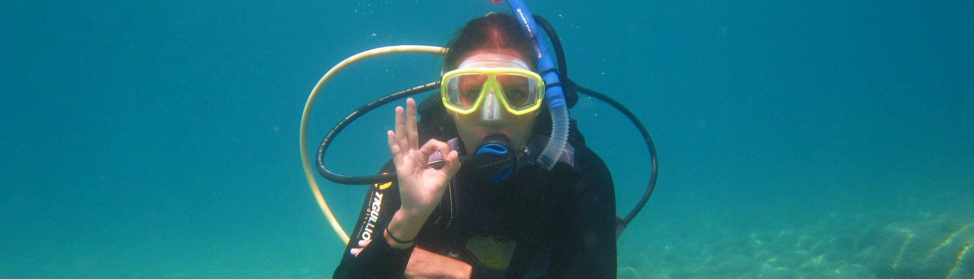 A participant or the Discover Scuba Diving at Santa Barbara Beach for Beginners with Hercules Marine Activities Corfu is posing for a photo during her first scuba dive in Corfu.