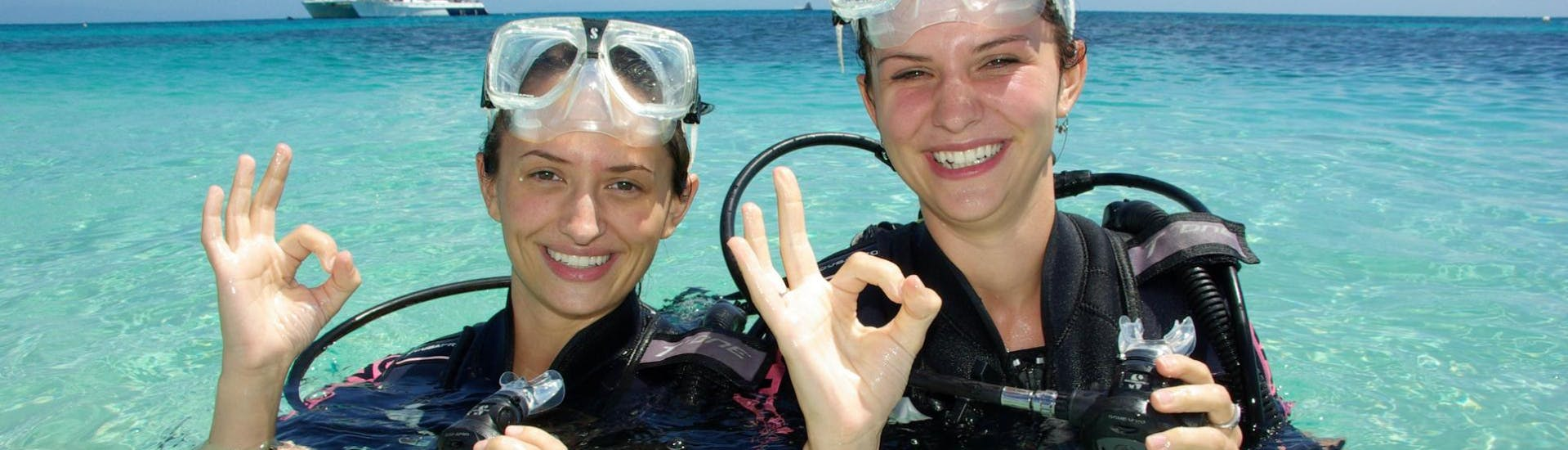 During the Discover Scuba Diving in the Great Barrier Reef from Cairns, two friends are feeling happy after their first dive under the guidance of a certified guide from Ocean Spirit Cruises.