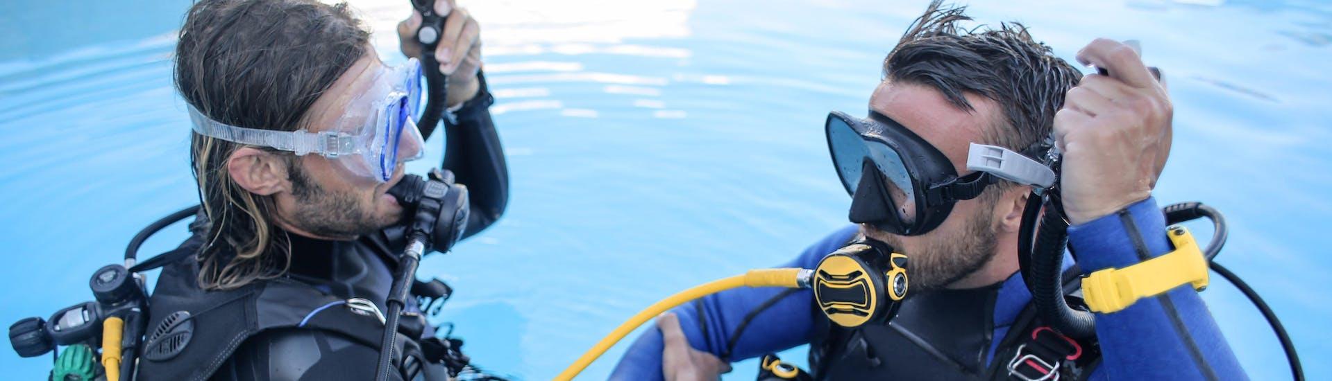 Als onderdeel van het proefduiken voor beginners leert een duikinstructeur een leerling hoe hij zijn duikuitrusting moet gebruiken in een zwembad.