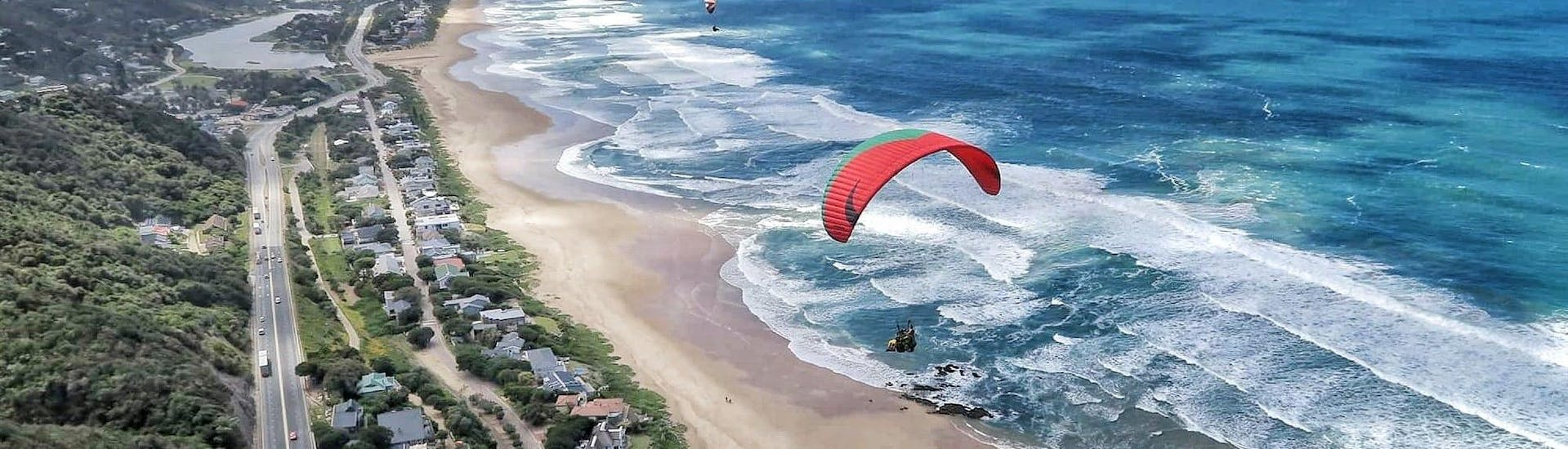 Experienced tandem pilot from Dolphin Paragliding Wilderness is flying with a client above the roaring ocean.