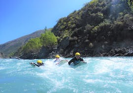 Two participants of the activity Drifting on the Kawarau River near Queenstown organized by Serious Fun Riverboarding are following ther guide on the river while riding some eddy lines.