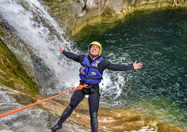 A young man is abseiling down a waterfall while canyoning in the Cetina River with Active 365.