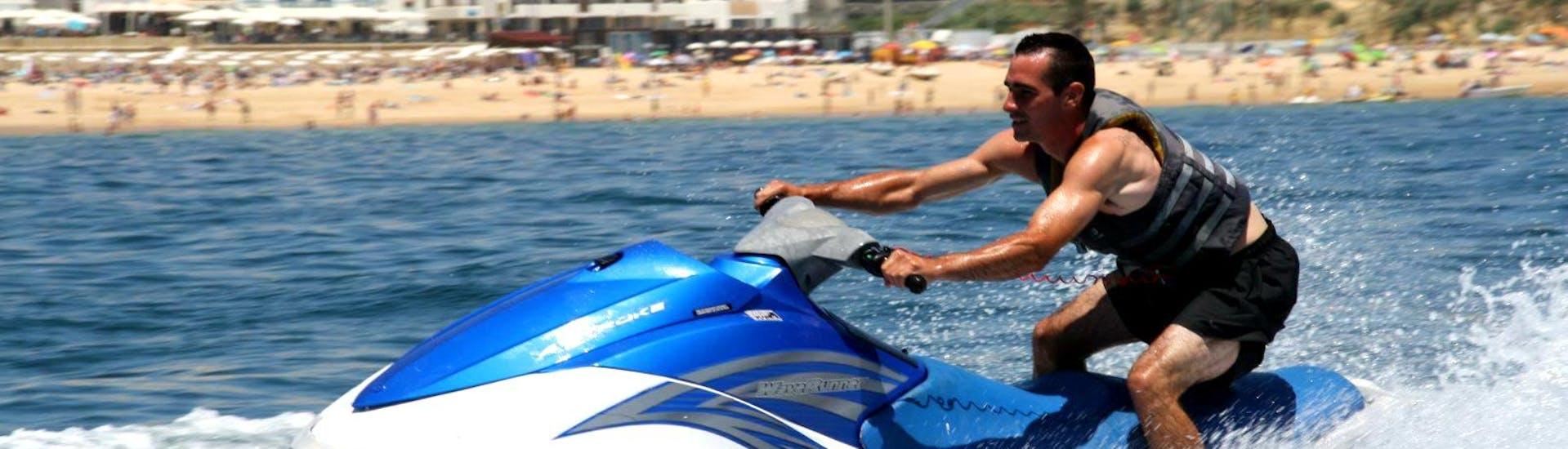 Ein Mann, der seinen wilden Ritt vor der Küste von Albufeira auf dem Duo Jetski genießt, das er von Dream Wave ausgeliehen hat.