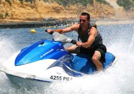 Un hombre deslizándose sobre la superficie del agua frente a la costa de Albufeira en una moto de agua duo que arrendó en la costa de Albufeira.