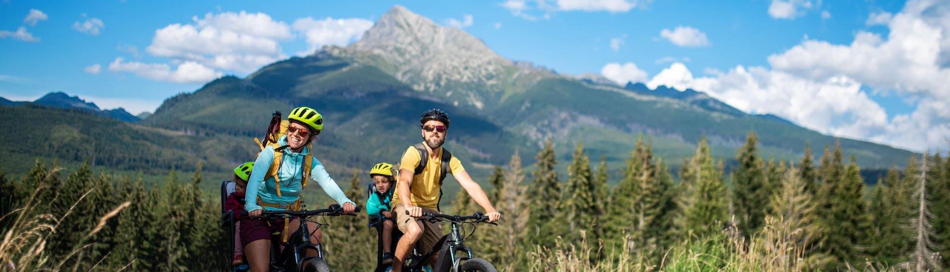 Eine Familie fährt mit ihren E-Bikes, die sie bei einem E-Bike Verleih gemietet hat, einen Bergweg entlang.