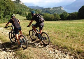 A local guide from Takamaka and a tourist make an Enduro electric mountain bike ride over the Lac du Bourget in Aix-Les-Bains.