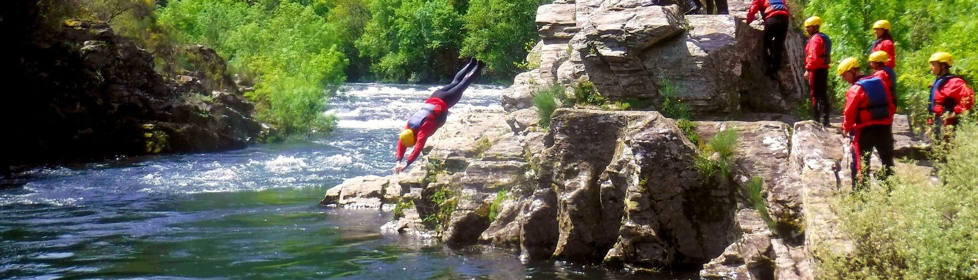 A participant of the Easy River Trekking in Rio Paiva in Arouca Geopark with Clube do Paiva is cliffjumping into the cool water of the river.