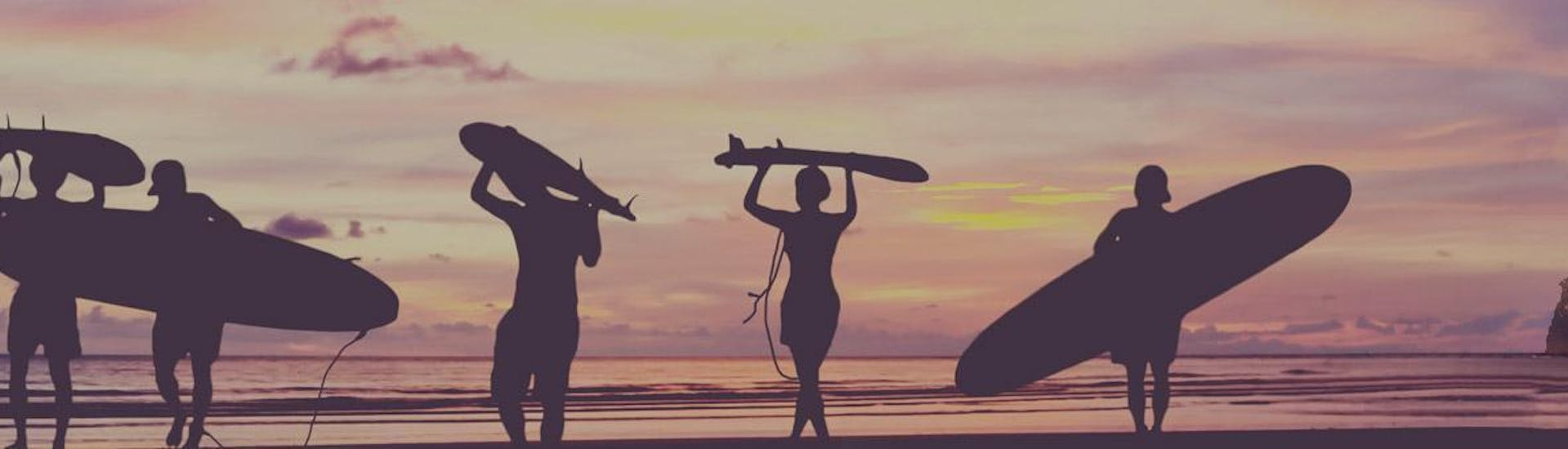Surfers are walking on the beach at sunset with their surf board on their head or under their arm at the end of their surfing lessons in Hendaye with the surf school École de surf Hendaia.