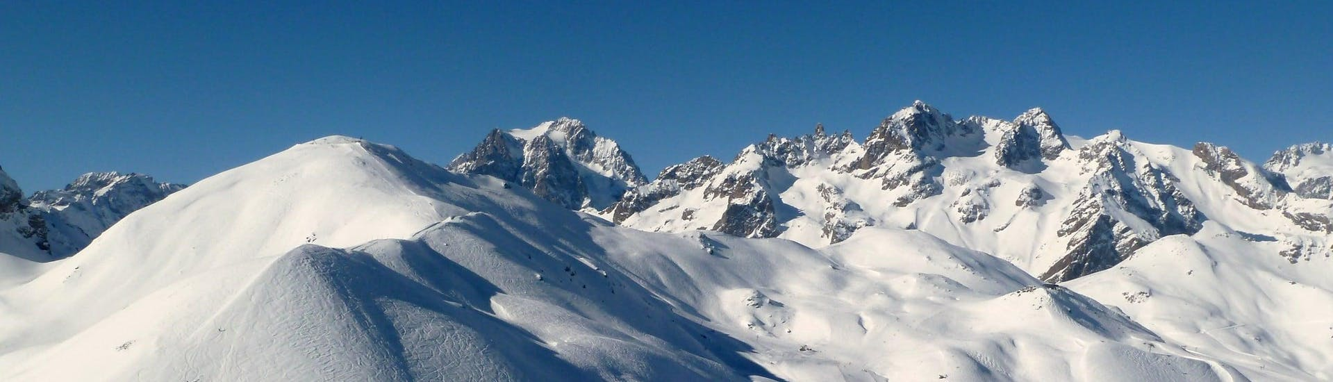 View over the sunny mountain landscape while learning to ski with the ski schools in Serre Chevalier Vallée.