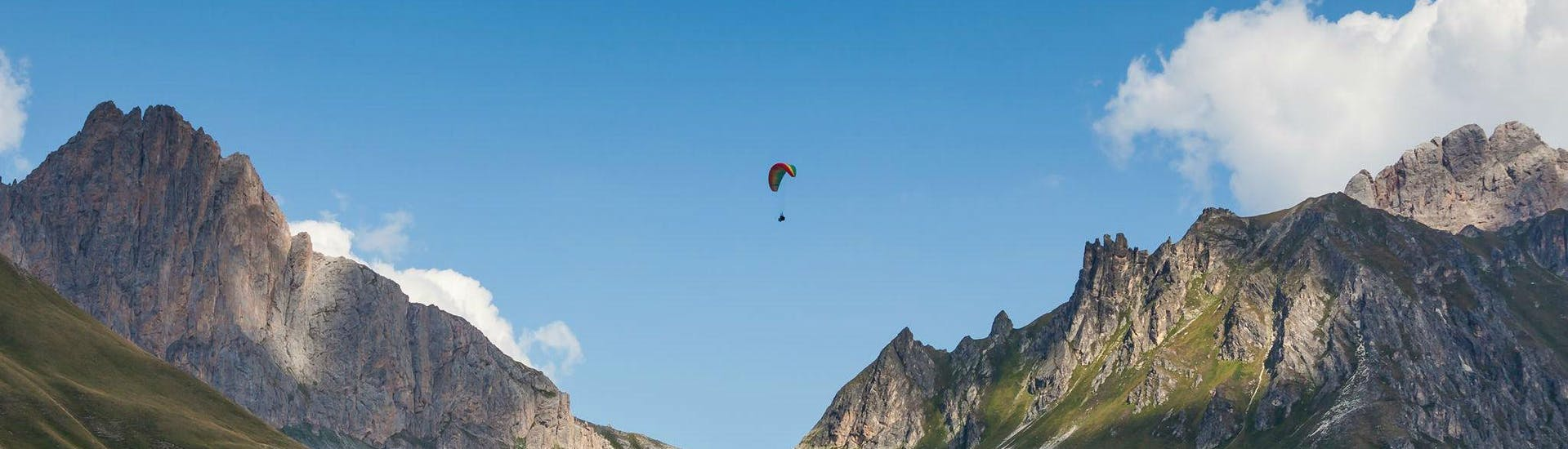 A paragliding pilot from Emotion'Air is flying high above Serre Chevalier during a tandem paragliding flight.