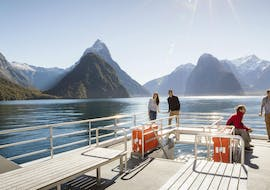 A group of people is standing on the outdoor viewing deck of one of the Southern Discoveries boat during their Encounter Nature Cruise in Milford Sound.