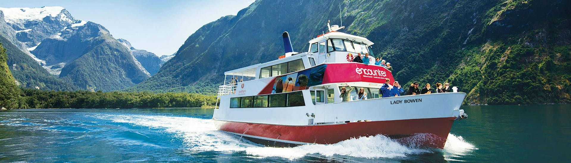 A Southern Discoveries ship is cruising along the beautiful New Zealand's most famous fjord during the Encounter Nature Cruise in Milford Sound.