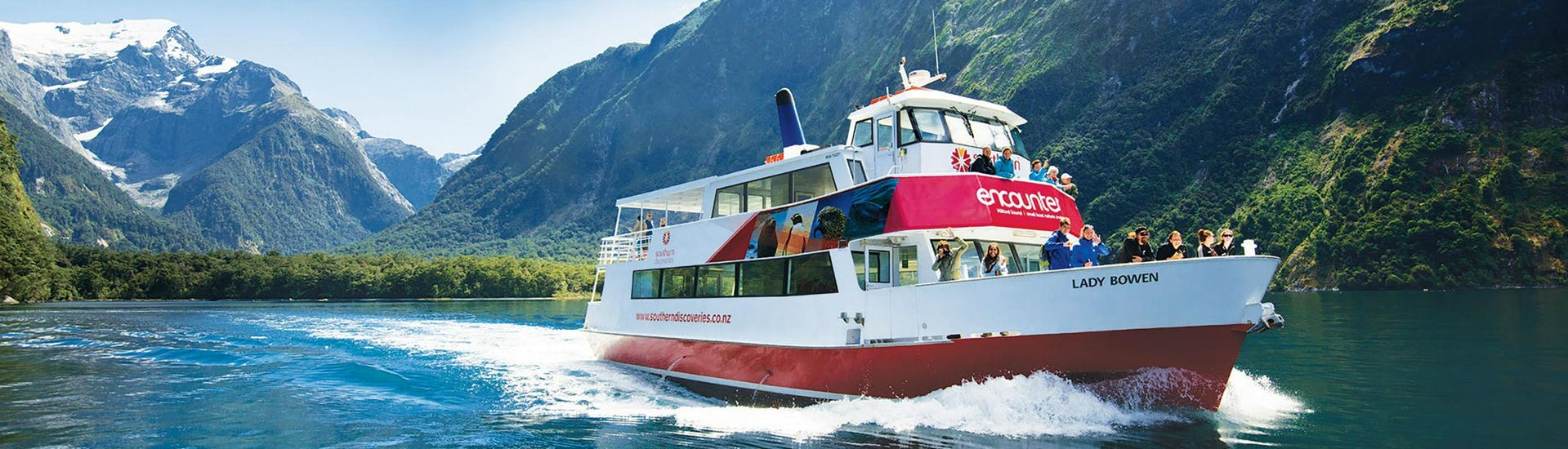 One of the Southern Discoveries ships is cruising along New Zealand's most famous fjord during the Encounter Nature Cruise in Milford Sound - Winter.
