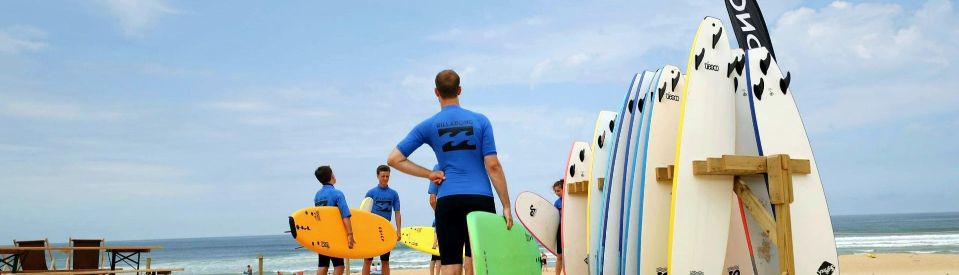 Participants are getting ready for their surfing lessons with the ESCF Anglet-Seignosse surf schools.