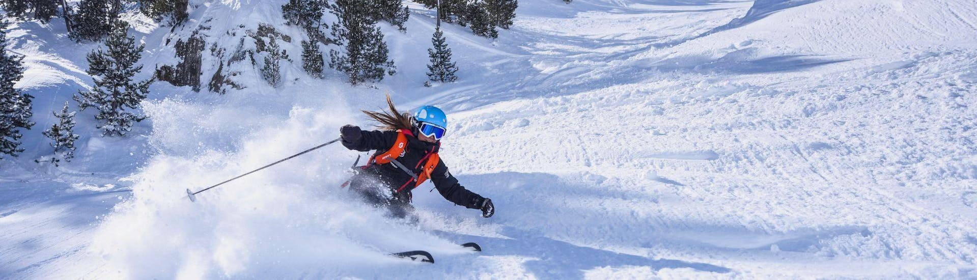 A ski instructor from Escuela Ski Cerler skies down the snowy slopes in a sporty and skillful way.