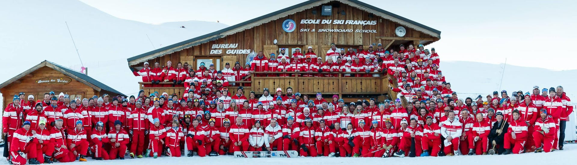 The entire team of the ski school ESF Alpe d'Huez is posing for a group picture in front of one of the chalet in the ski resort Alpe d'Huez.