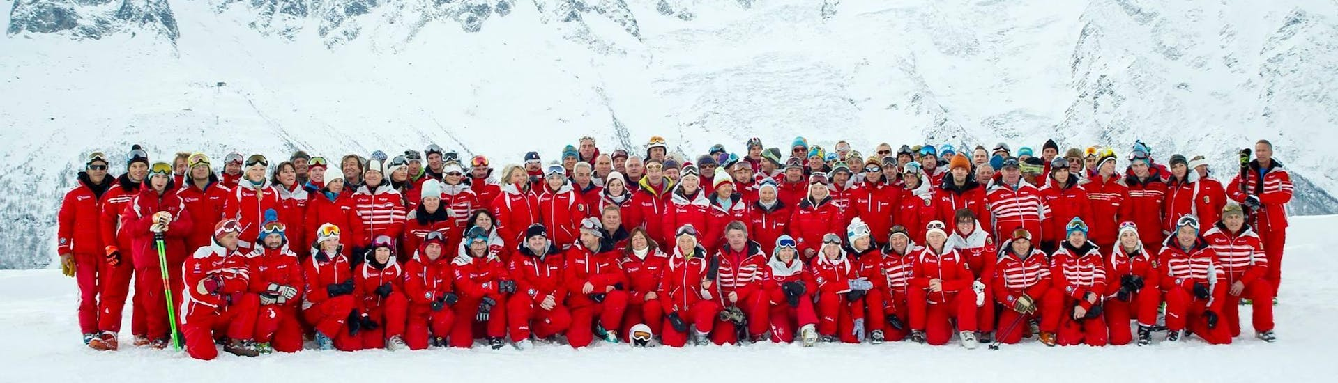 The whole team of the ski school ESF Chamonix is posing for a picture in front of a snow-covered mountain.