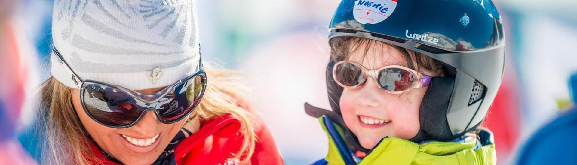 A child is having fun with her private instructor while learning how to ski in the ski school ESF Val d'Isère located in the ski resort Val d'Isère.