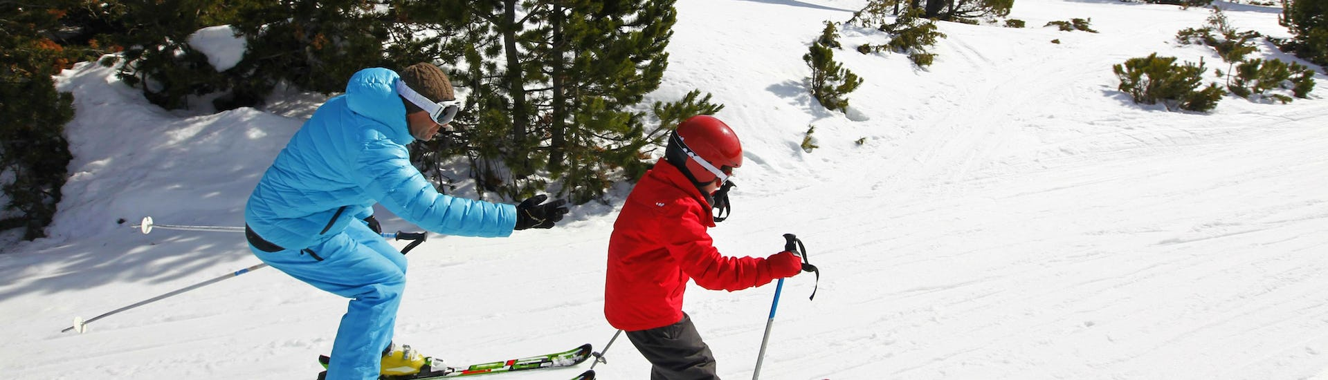 A young skier is following the instructions of his ski instructor from the ski school ESI Font Romeu on one of the snowy tracks of the Font Romeu ski resort in the Pyrenees.