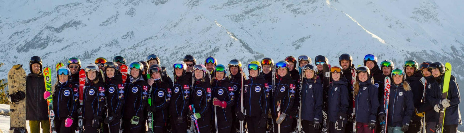 The ski instructors from the ski school European Snowsport Chamonix are posing together on top of one of the many pistes in the ski resort of Chamonix.