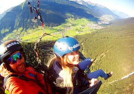 """A girl flies together with her tandem pilot from Fly-Stubai over the beautiful mountain world and smiles happily into the camera during the offer """"Extended High Altitude Tandem Paragliding in Stubaital""""."""