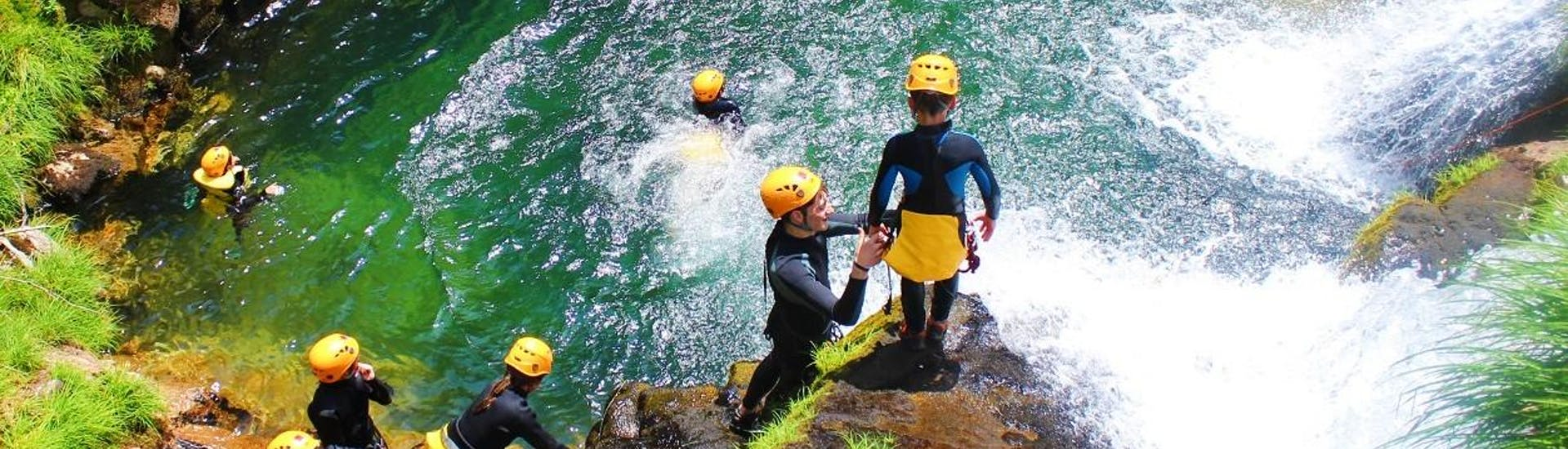 A guide is helping a young boy to prepare for a jump during the Family Canyoning in Ribeira de Vessadas in Arouca Geopark with Clube do Paiva.