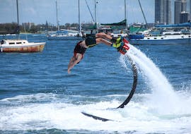 Under the guidance of an experienced instructor from Gold Coast Watersports, a young man is trying some tricks on a Flyboard in Gold Coast.