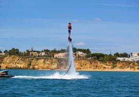 While Flyboarding at Praia de Armação de Pêra with Moments Watersports Algarve, a young man is flying high above the sea and enjoying the view of the beautiful Algarve coast from up in the air.