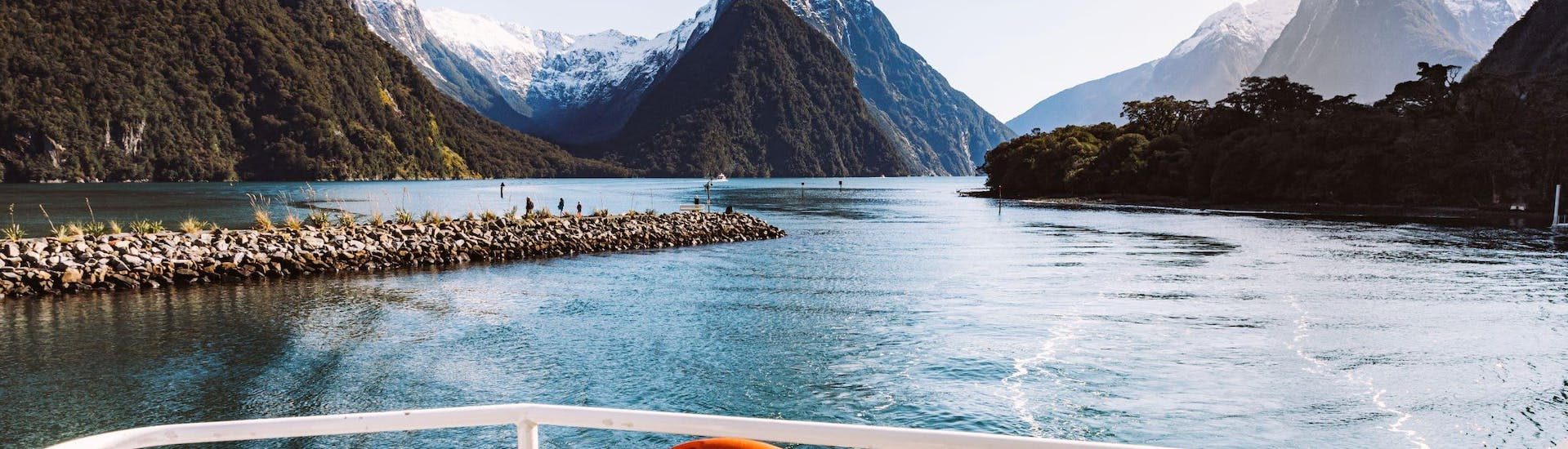 Durign the Flying Tour with Milford Sound Cruise - From Queenstown, a catamaran from Jucy Cruise is leaving the stunning mountainous landscape behind.