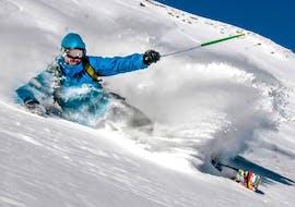 Un skieur ski de mqnière sportive sur les pistes durant son cours particulier de ski pour adultes - tous niveaux avec l'école de ski Freedom Snowsports.