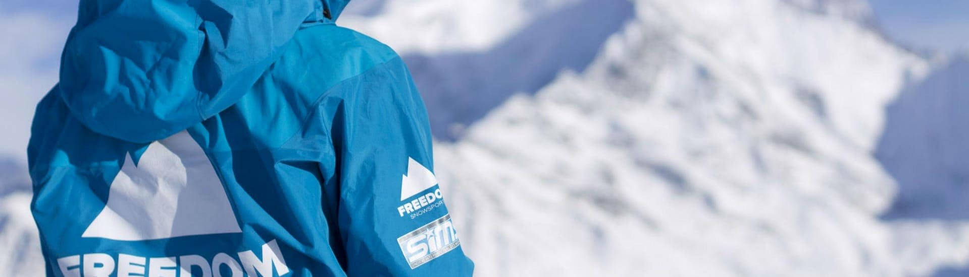 Eine Skilehrerin der Skischule Freedom Snowsports blickt über die verschneite Berglandschaft im Skigebiet Chamonix.