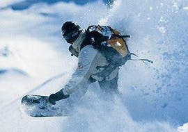 """A snowboarder makes a jump and lets the snow splash into the air during the off-piste snowboarding lessons """"Package"""" - All levels of the snowboard school BOARD.AT"""