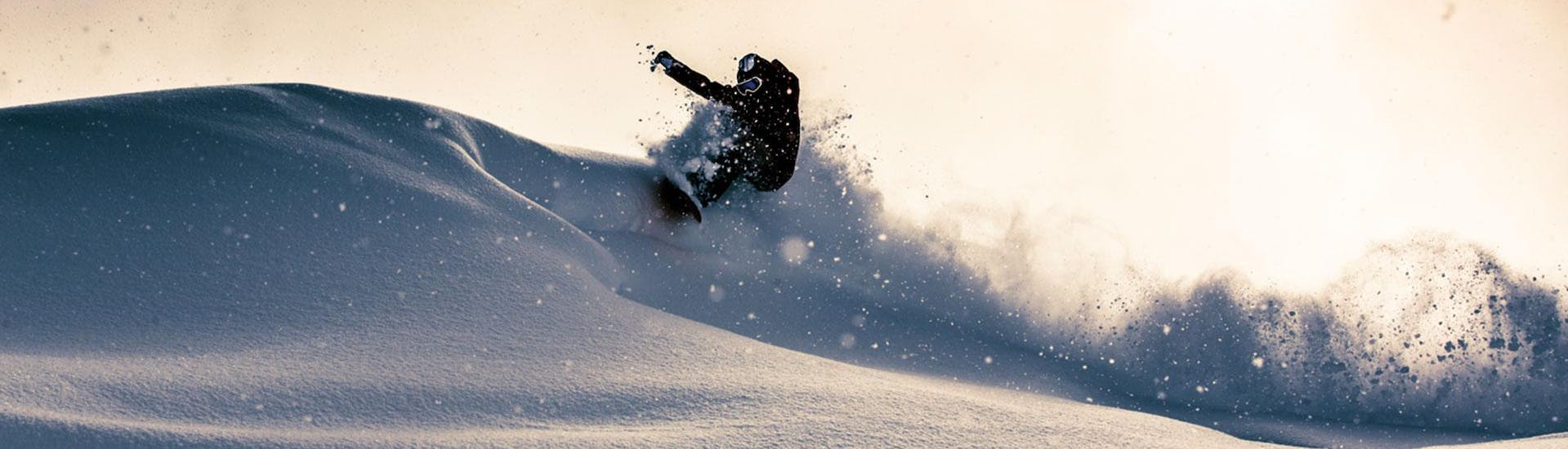 A snowboarder is riding through deep powder snow during his Off-Piste Snowboarding Lessons - All Levels with BOARD.AT.