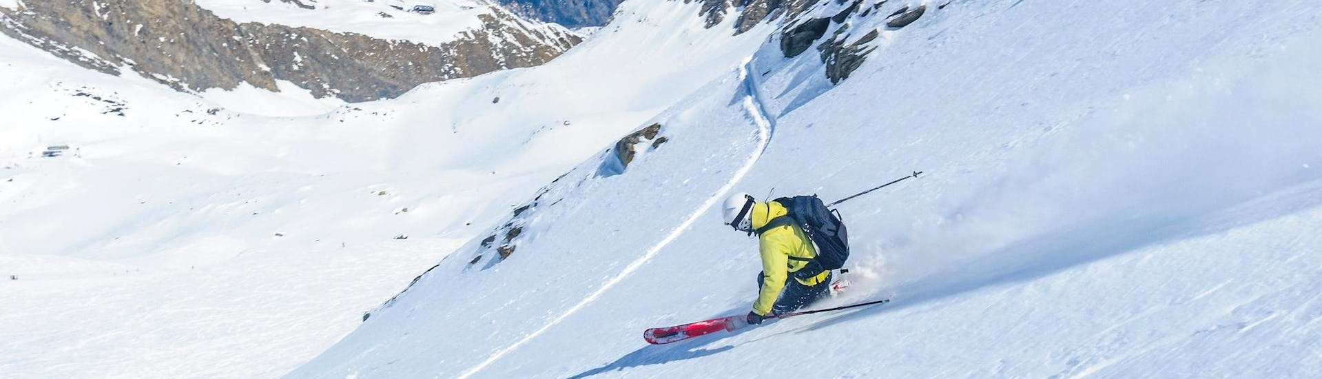 A freeride skier is skiing through the powder snow during one of the Private Off-Piste Skiing Lessons - Advanced organised by Alpinist.