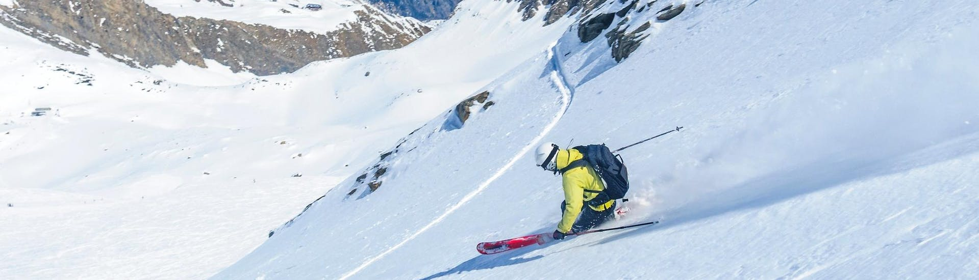 A freeride skier is skiing through the powder snow during one of the Freeriding -- Surf your perfect line with ROCKnSNOW organised by ROCKnSNOW Alpine Guiding.