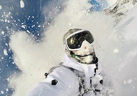"""A snowboarder rides through a big cloud of snow and gives everything on the piste as part of the offer """"Private off-piste Snowboard lessons - All Levels"""" of the snowboard school BOARD.AT."""