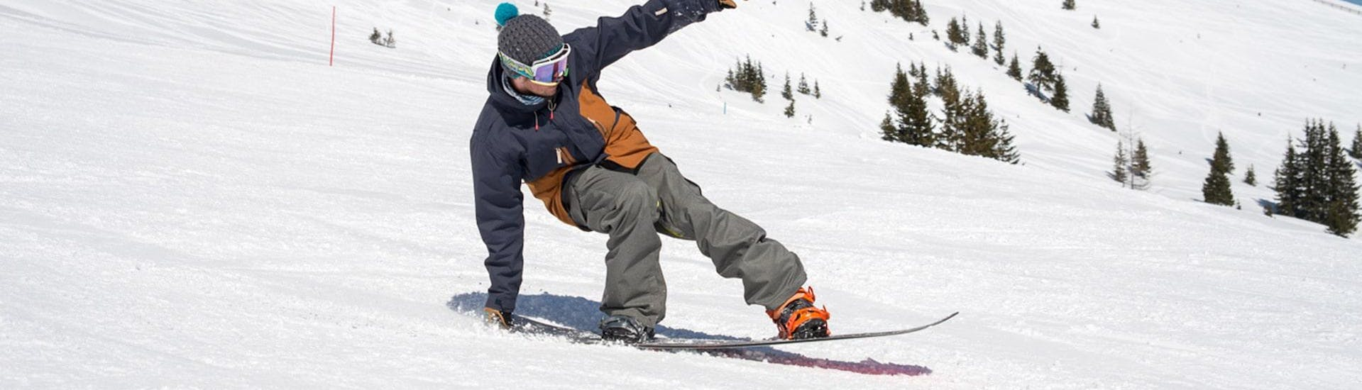 A snowboarder is practicing his freestyle moves during one of the Freestyle Snowboarding Lessons - All Levels with BOARD.AT.