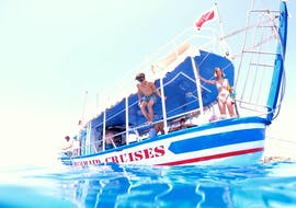 During a Full-Day Cruise to Gozo, Blue Lagoon & Comino with Mermaid Cruises Malta, a young passenger is jumping into the blue sea to go snorkeling in the clear water.