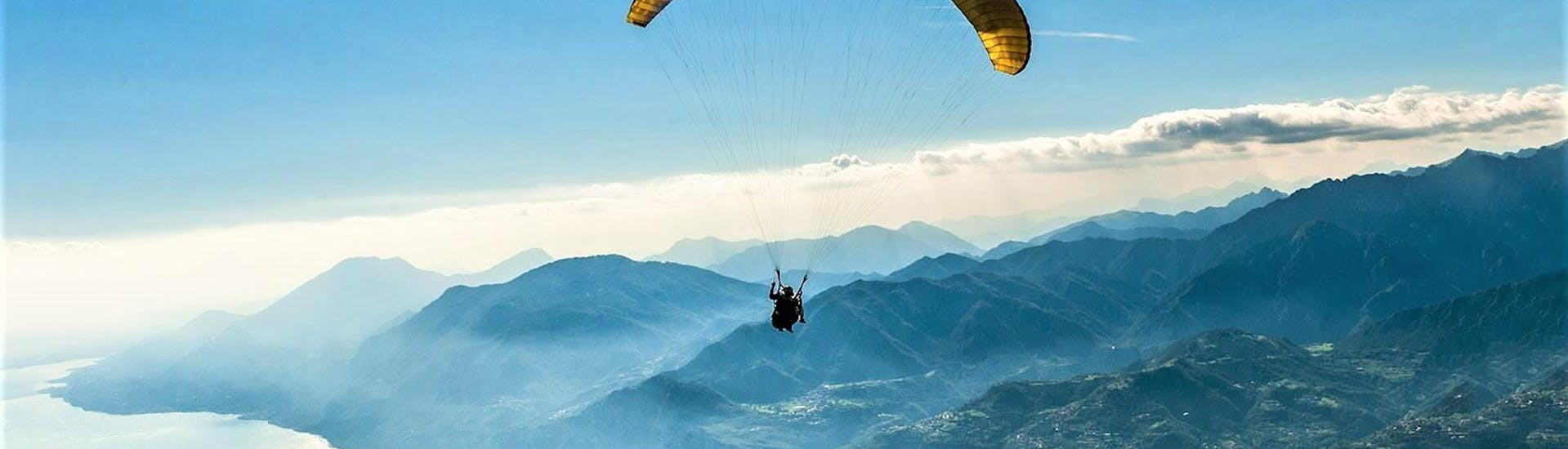 A tandem paragliding pilot is flying above the Garda Lake during the flight Tandem Paragliding on Lake Garda - Monte Baldo organized by the centre GardaAirStyle.