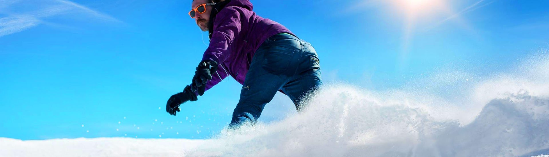 Snowboarder takes a tight turn on a sunny day during his Private Snowboarding Lessons for Kids & Adults - All Levels with the ski school Skischule Thomas.