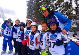 Kinder zeigen stolz ihre Medaille nach dem erfolgreichen Rennen während dem Kinder Skikurs (6-12 Jahre) - Ganztags - Alle Levels mit der Skischule Zugspitze-Grainau.