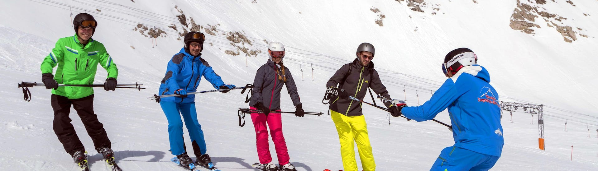 Ski instructor explains to the course participants how to warm up during the Ski Lessons for Adults - All Levels with the ski school Skischule Zugspitze-Grainau.